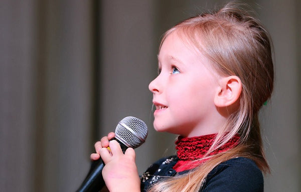 Photo of a girl speaking into a microphone