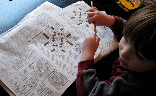 Photo of a boy doing a newspaper crossword