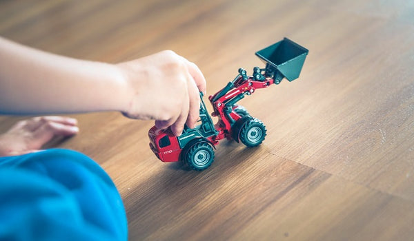 Photo of a child playing with a toy dumper truck