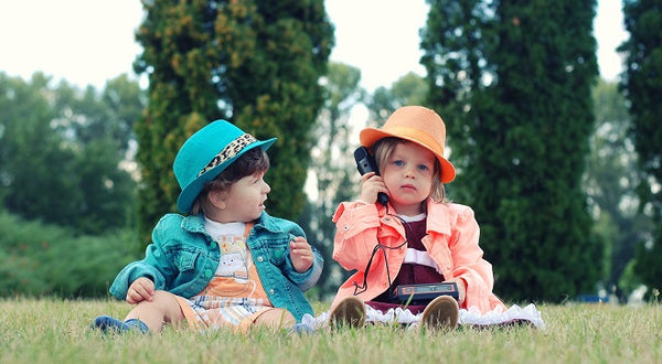 Two children using a telephone outdoors
