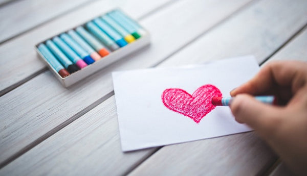 Photo of a child drawing a heart on a card