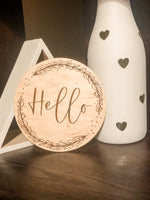 Load image into Gallery viewer, hello, wreath, script, font, typography, welcome sign, baby sign, nursery, home decor, wood decor, maple, wood, engraved, laser engraved, made in the USA, made in America, made in Oklahoma, handmade, small business, ki+three, kids room, personalization, light wood, announcement, baby announcement