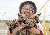 smiling woman holding baby foxes