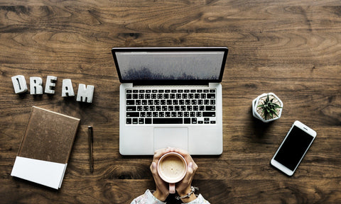 Laptop, phone, notebook and cup of coffee in woman's hands, working hard, being productive