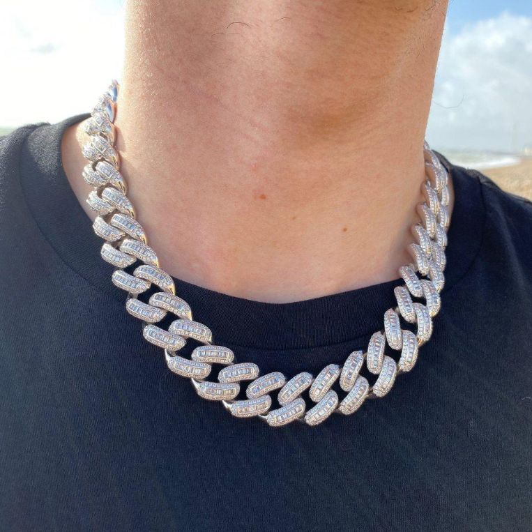 19mm LFY ICED Baguette Cuban Chain in White Gold shown being worn around a man's neck on a beach, best out.
