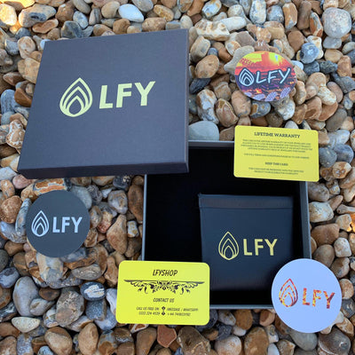 LFY packaging including lifetime warranty card, contact us card, stickers, box, leather pouch on the beach on top of pebble stones.
