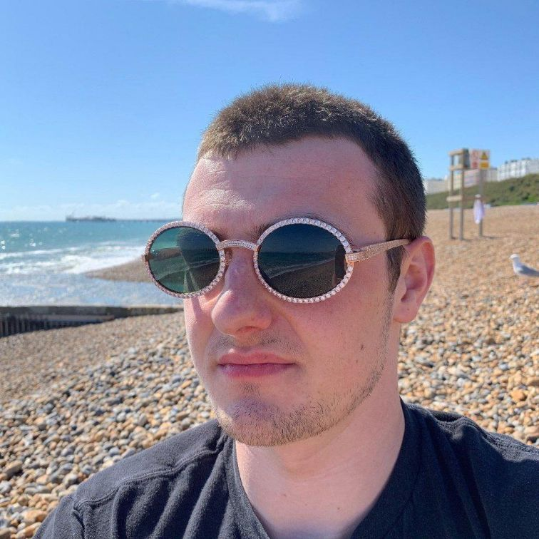 LFY ICED Baller Sunglasses in Rose Gold (Green Tint) shown being worn by a man on the beach, best out