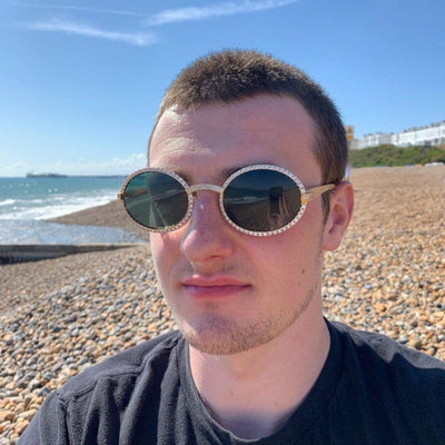 LFY ICED Baller Sunglasses in Gold (Green Tint) shown being worn by a man on the beach, best out