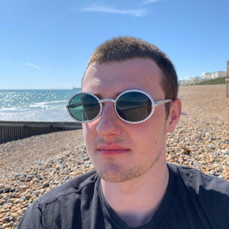 LFY ICED Baller Sunglasses in White Gold (Green Tint) shown being worn by a man on the beach, best out