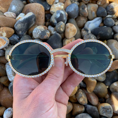 LFY ICED Baller Sunglasses in Gold (Green Tint) front of the glasses being shown on a beach, best out