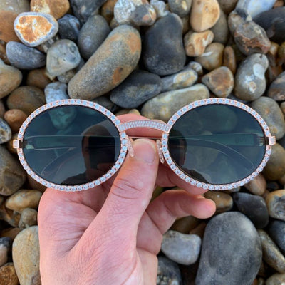 LFY ICED Baller Sunglasses in Rose Gold (Green Tint) front of the glasses being shown on the beach, best out