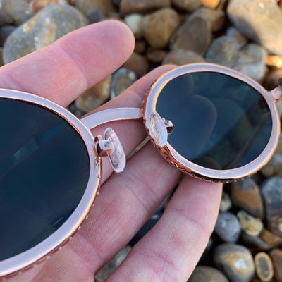 LFY ICED Baller Sunglasses in Rose Gold (Green Tint) glasses being shown up close and from an angle, on the beach, best out