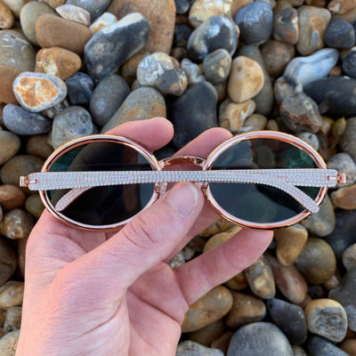 LFY ICED Baller Sunglasses in Rose Gold (Green Tint) back of the glasses being shown on the beach, best out