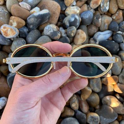 LFY ICED Baller Sunglasses in Gold (Green Tint) back of the glasses being shown on the beach, best out