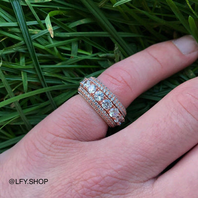 ICED 5 Layer Spinning Ring in Rose Gold shown being worn on the pinky fingers with a grass background, best out.