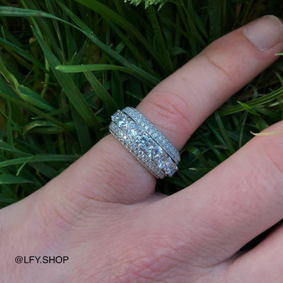 ICED 5 Layer Spinning Ring in White Gold shown being worn on the pinky finger with a grass background, best out.