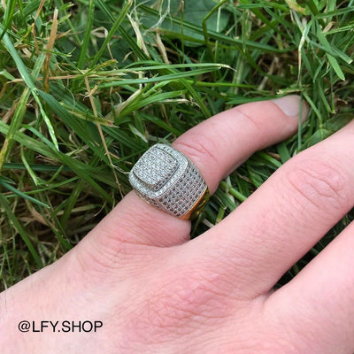 ICED Baller Ring in Gold, shown being worn on the pinky finger with a grass background,  best out