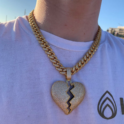 ICED Broken Heart Pendant in Gold (GREEN CENTRE) shown being worn on a man on the beach, best out