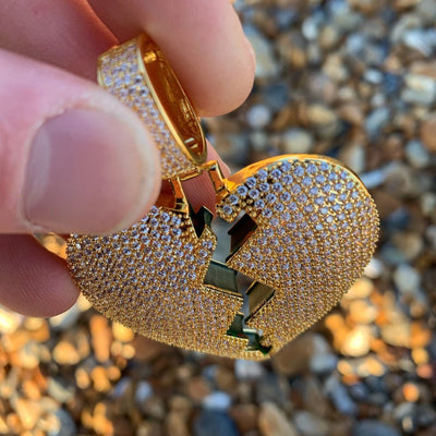 ICED Broken Heart Pendant in Gold (GREEN CENTRE) shown being held by a man on the beach, best out