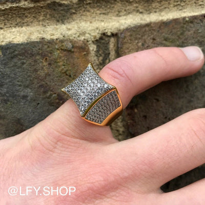 ICED Champ Ring in Gold shown being worn on the pinky finger in front of a brick background, best out.