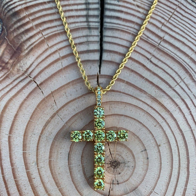 ICED Glowing Birdie Cross Pendant in Gold (YELLOW CZ) shown against a wooden background, best out