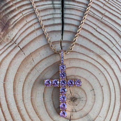 ICED Glowing Cross Pendant in Rose Gold (PINK CZ) shown on a wooden background, best out
