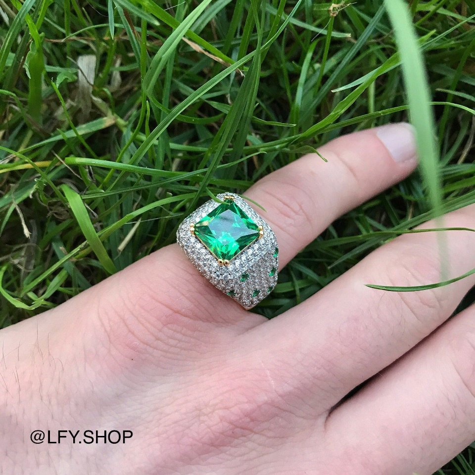 ICED Green Beast Ring in Gold shown being worn on the pinky finger with a grass background, best out.