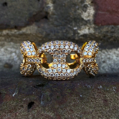 ICED Master Ring in Gold, front of the ring being shown against a brick wall, best out.