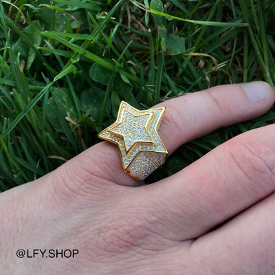 ICED Star Ring in Gold shown being worn on the pinky finger with a grass background, best out.