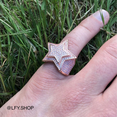 ICED Star Ring in Rose Gold shown being worn on the pinky finger with a grass background, best out.