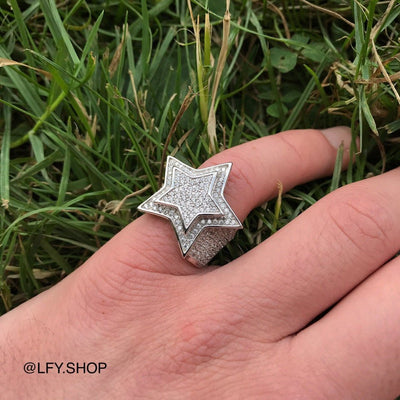 ICED Star Ring in White Gold shown being worn on the pinky finger on a grass background, best out.