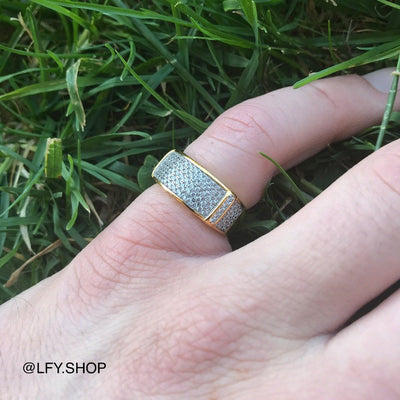 ICED Tiger Ring in Gold shown being worn on the pinky finger with a grass background, best out.