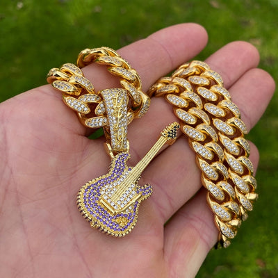 LFY ICED Guitar Pendant in Gold shown on a chain in a man's hand, best out