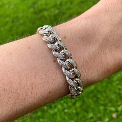 (NEW DESIGN) 12mm ICED Cuban Bracelet in White Gold being shown on a man's wrist, best out.