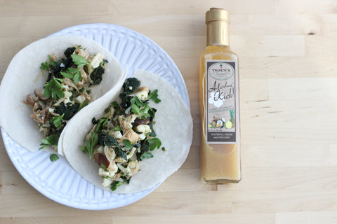 White plate with two jack fruit and kale tacos and bottle of Aloha Kick salad dressing and marinade