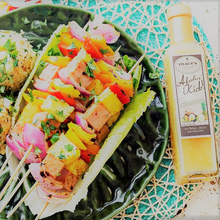 Delicious veggie shrimp kabobs with bottle of pineapple vinaigrette beside it on the table