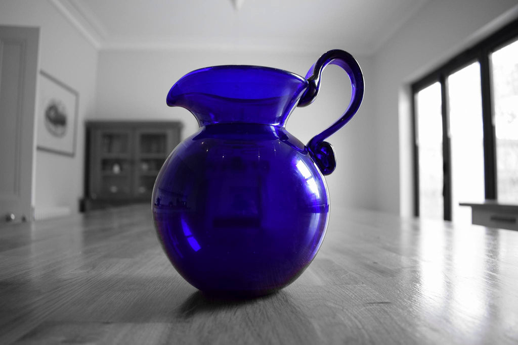 A blue glass milk jug on a kitchen table