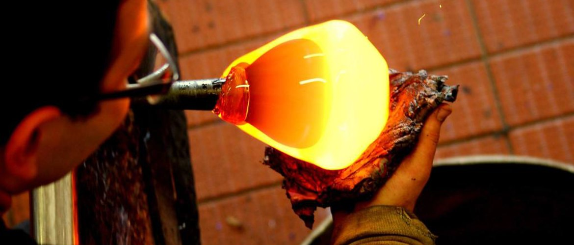 Molten glass being shaped in the hot floor workshop