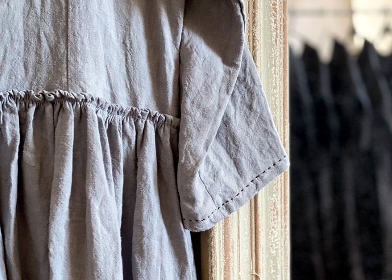 Close up of hand stitched detail on grey linen dress