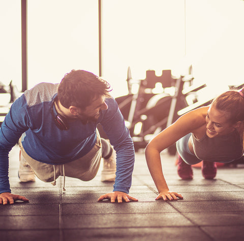 Man and woman in a gym, each in push-up position