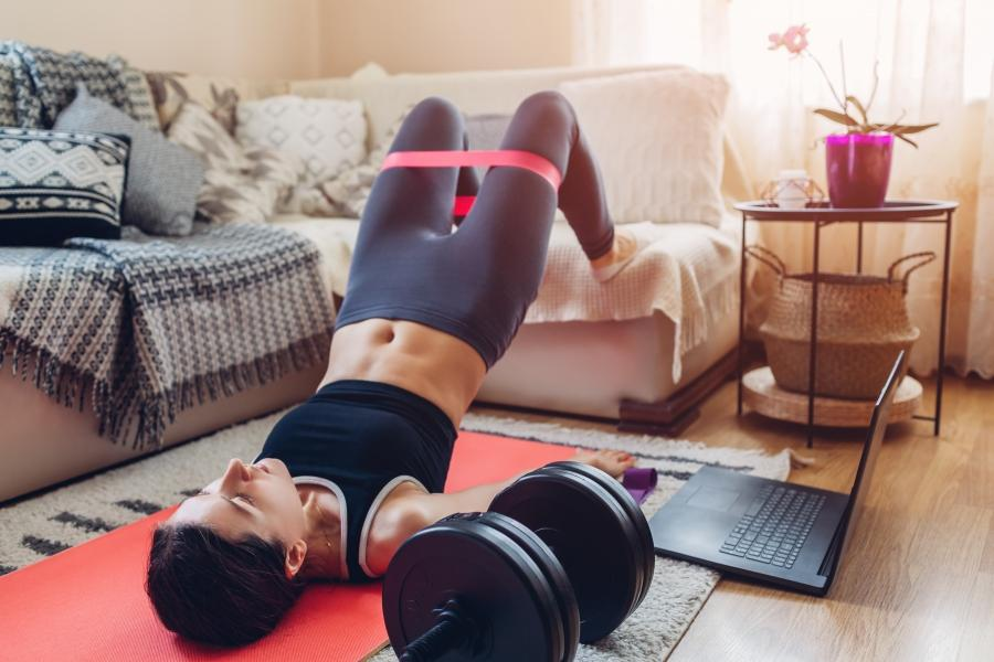 Woman working out at home with resistance bands.