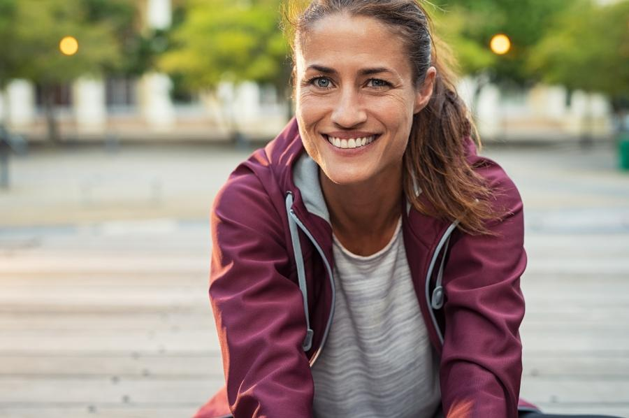 Woman sitting on the sidewalk after going for a run.