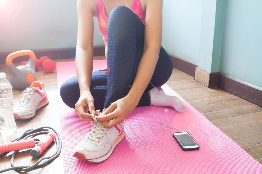 Woman tying her shoe getting ready to workout at home.