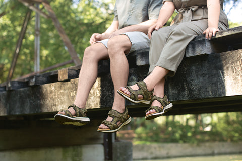 A man and woman sit on a bridge above some water in waterproofed SAS sandals