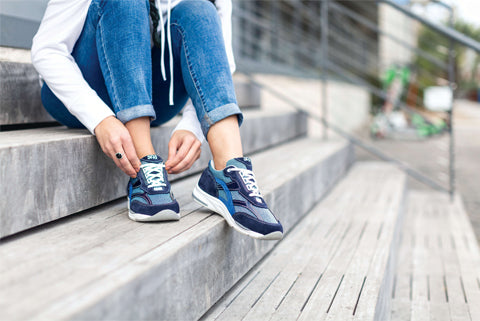 A woman ties her shoes carefully while sitting on steps