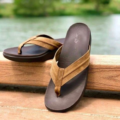 A pair of SAS sandals balanced on a wooden dock near a lake