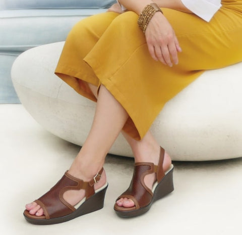 The lower half of a woman wearing mustard-yellow pants and brown comfortable dress sandals