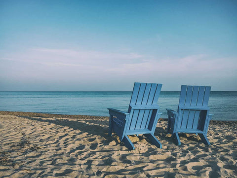 Two wooden blue chairs sitting on a sandy beach facing the ocean