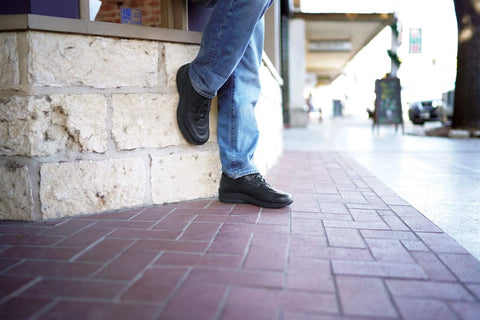 A person wearing slip-resistant shoes for men and leaning against a wall on break