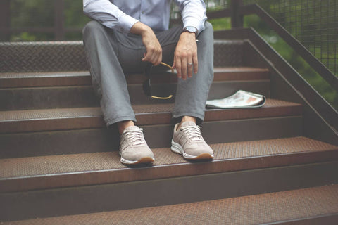 Man sitting on stairs outdoors wearing stylish SAS comfort shoes